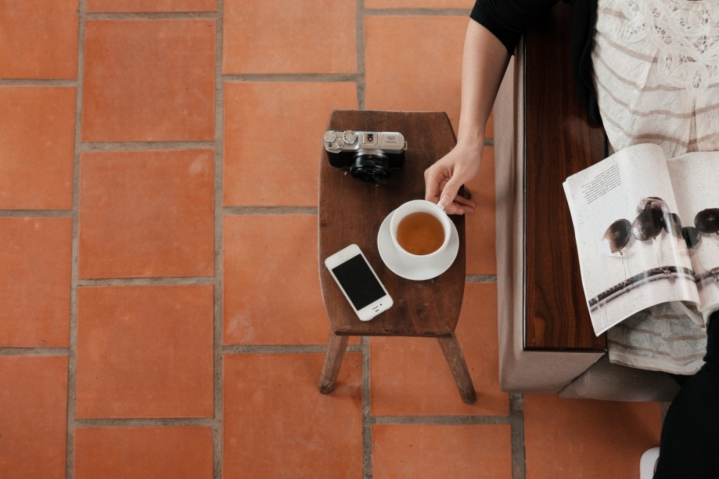 https://consultantsconsultant.com.au/wp-content/uploads/2018/02/brown-woman-reading-magazine-iphone-coffee-quarry-tiles.jpg